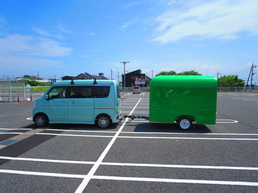 軽自動車と軽キャンピングトレーラーの食料買い出しのスーパー駐車場