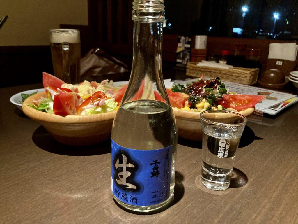 日帰り温泉施設「かんなの湯」の居酒屋の神楽の日本酒とシーザーサラダと海藻サラダ